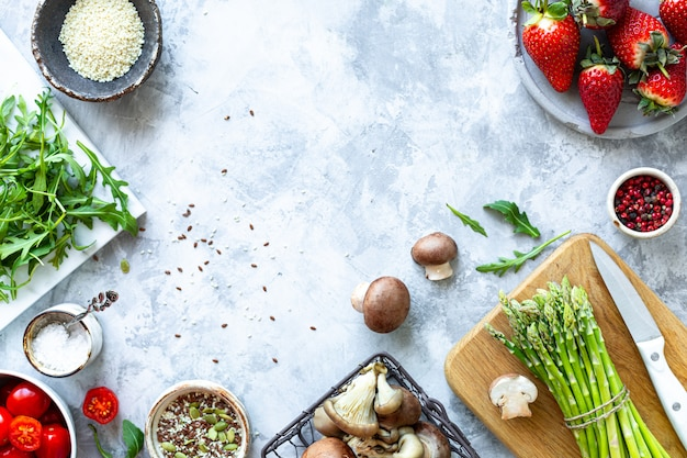 Ingredients for cooking on a gray concrete background. a bunch of fresh green asparagus, strawberries, mushrooms, tomatoes, arugula. top view. copy space