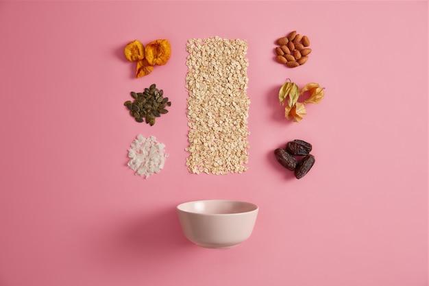 Ingredienti per cucinare una sana colazione. farina d'avena, albicocca secca, physalis, datteri, semi di zucca, mandorle, cocco aggiunti al tuo porridge. nutrizione organica, superfood, concetto di spuntino nutriente