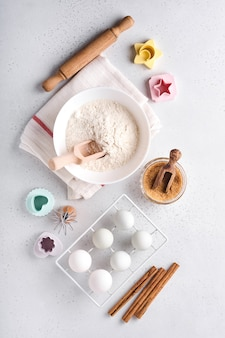 Ingredients for cooking homemade baking. baking background with flour, eggs, kitchen tools, utensils and cookie molds on white marble table. top view. flat lay style. mock up.