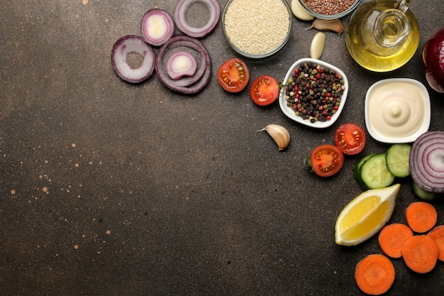 Ingredients for cooking salad. various vegetables and spices carrots, tomatoes, onions, cucumbers, peppers and arugula on a dark background. top view.