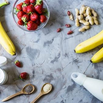Ingredients for cooking smoothies from strawberries, bananas, milk, yogurt, chia seeds