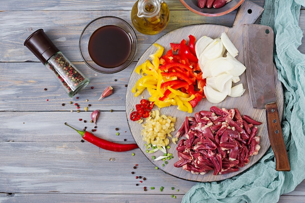 Ingredients for cooking stir-fry from chicken hearts, paprika and onions. chinese cuisine. top view