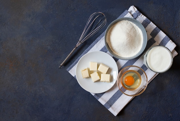 Ingredients for crepes and pancakes on a dark background. flour, egg, milk, butter, whisk. top view. space for text.