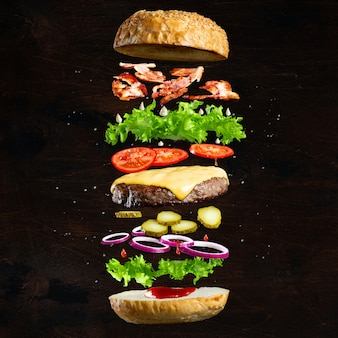 Ingredients of a delicious burger with ground beef patty, lettuce, bacon, onions, tomatoes and cucumbers