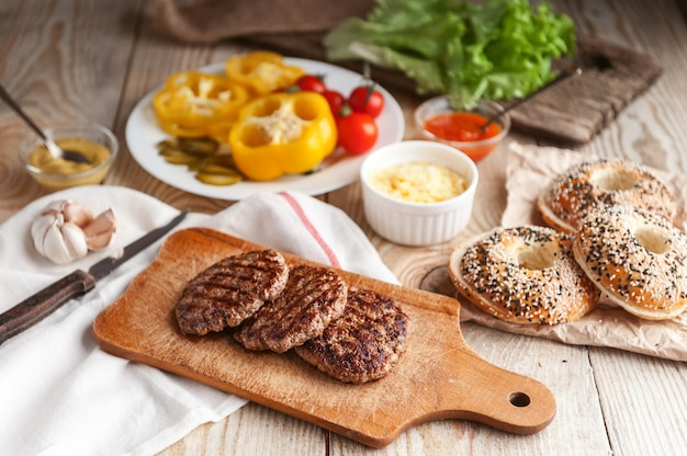Ingredients for a delicious home burger. roll, bagel, with a juicy cutlet from beef, sauces cheese fresh lettuce leaves