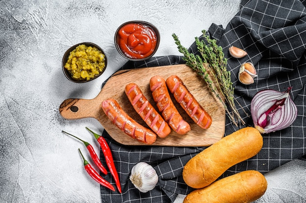Ingredients for different homemade hot dogs, with fried onion, chili, tomatoes, ketchup, cucumbers, and sausage