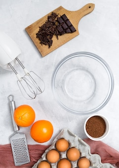 Ingredients; electric mixer; hand grater and empty bowl for preparing the chocolate cake on white surface