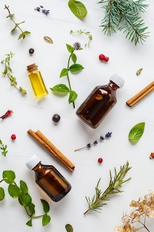 Ingredients for essential oil. different herbs and bottles of essential oil, white background, flatlay.