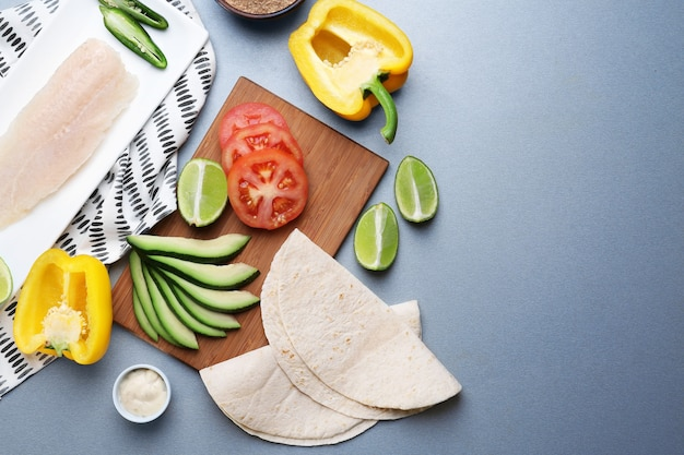 Ingredients for fish tacos on grey table