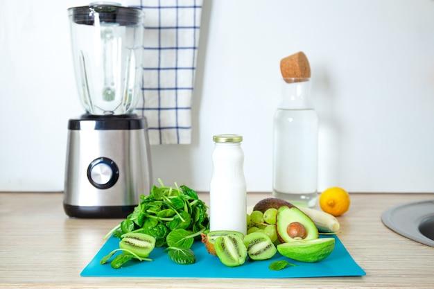 Ингредиенты для зеленого смузи. бирюзовый фон банана, шпината, семян чиа, кокосового молока в стеклянной банке, авокадо, винограда. детокс, рецепт смузи для здорового питания.