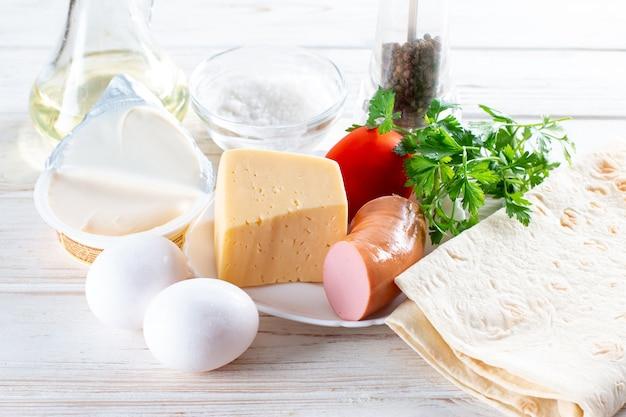 Ингредиенты для здорового завтрака. яйца, сыр, овощи, хлеб, сосиски, молоко. приготовление омлета, рулета, лаваша