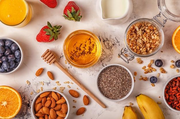 Ингредиенты для здорового завтрака - мюсли, мед, орехи, ягоды и фрукты.