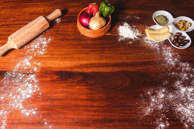 真ん中にスペースのある木製のテーブルに置いたピザの材料。