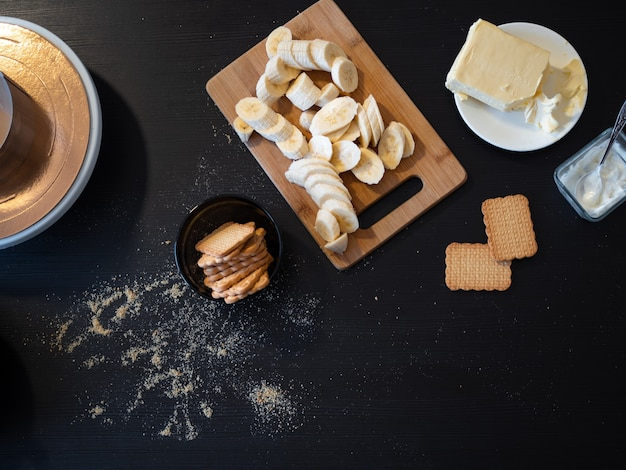 Ингредиенты для песочного торта с бананом и карамелью, черный деревянный стол на кухне, продукты, приготовленные на вкусный десерт со сливками, домашняя кухня