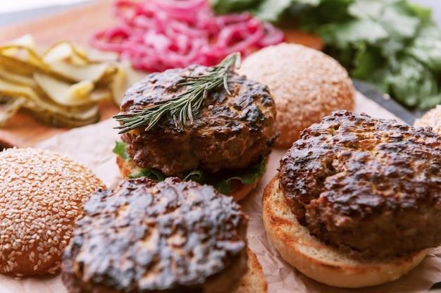 牛肉の大きなチョップを備えた素朴なスタイルの美味しくてジューシーなハンバーガーホームの材料