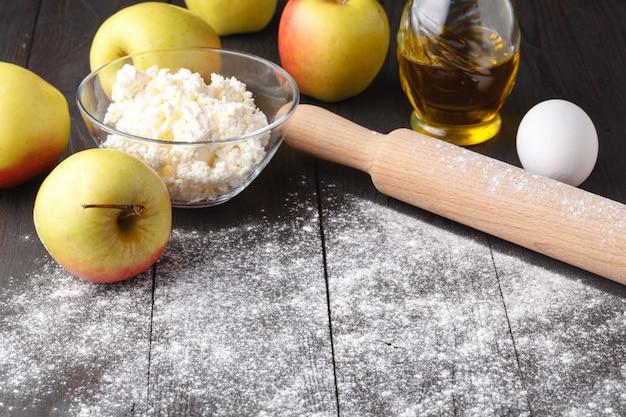 Ингредиенты для приготовления яблочного пирога. свежее яблоко, масло, мука, сахар, специи на деревенском дереве.