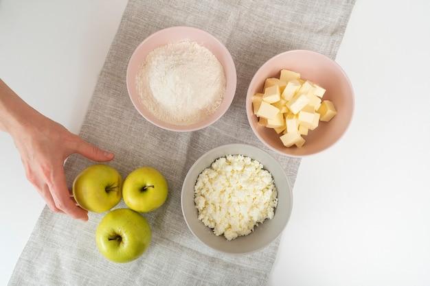 アップルパイの材料。小麦粉、バター、カッテージチーズ、リンゴのプレート。上面図。