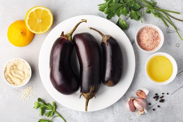 Ингредиенты для баба гануш бабагануш или хумус из баклажанов на миске