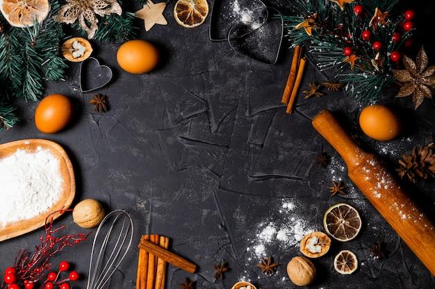 黒の背景、平面図、コピースペースでクリスマスクッキーを焼くための成分。