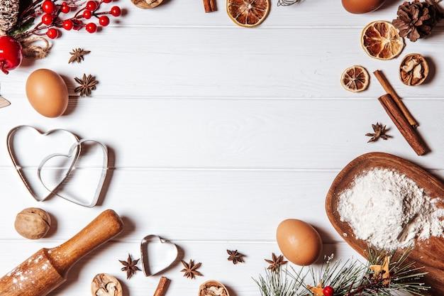 Ингредиенты для выпечки рождественского печенья на белом деревянном фоне, копией пространства.