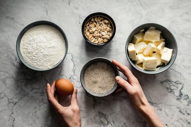 쿠키 베이킹 재료. 밀가루, 설탕, 바닐라, 소금, 버터, 땅콩, 계란. 상위 뷰 가로 사진, 대리석 배경