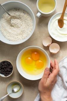 ベーキング、デザートまたはペストリーの調理用の材料。上面図、小麦粉、砂糖、卵、油、チョコレートチップを入れたボウル。