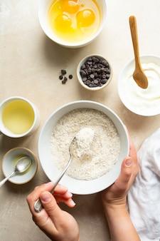 ベーキング、デザートまたはペストリーの調理用の材料。上面図、白い小麦粉のボウルを持っている女性の手。