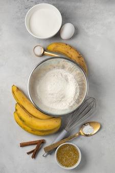 ライトグレーの背景上面図のボウルにバナナブレッドの材料