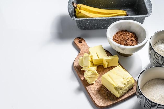 バナナブレッドレシピの材料。バナナ、チョコレート、小麦粉、卵、砂糖、バター、チョコレート。白色の背景。上面図。スペースをコピーします。