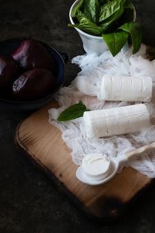 ビートルートサラダの材料:ビートルート、ヤギのチーズ、ほうれん草。料理、準備、ベジタリアン、きれいな食事、健康食品のコンセプト。素朴な背景。上面図。フラットレイ
