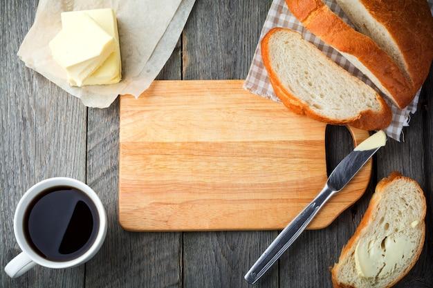 朝食の材料。古い木の表面の中央に木の板が付いているパン、バターおよび一杯のお茶
