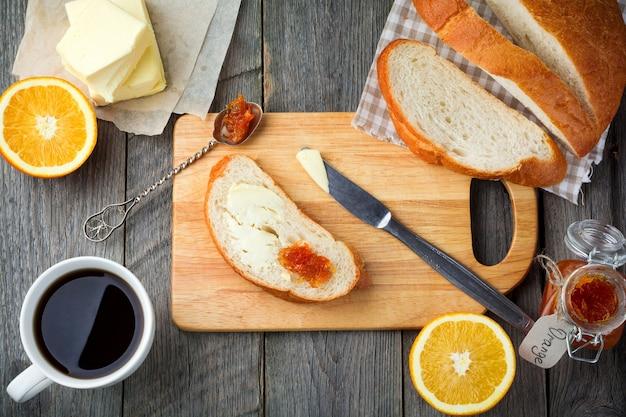 朝食の材料。パン、バター、オレンジマーマレード、古い木の表面の中央に木の板が付いたお茶