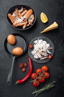 Ингредиенты для завтрака омлет с крабовым мясом и сыром, на черном фоне, плоский вид сверху