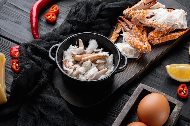 黒い木製のテーブルにカニ肉とチーズをセットした朝食オムレツの材料