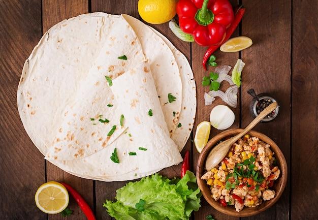 Ингредиенты для буррито обертывают куриное мясо, кукуруза, помидоры и перец на деревянный стол. вид сверху Premium Фотографии