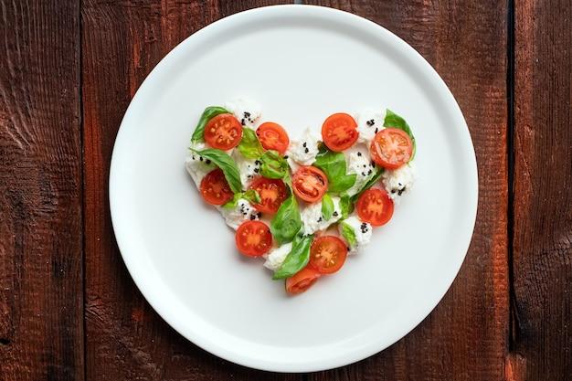 Ингредиенты для салата капрезе в форме сердечка. символ любви к итальянской кухне