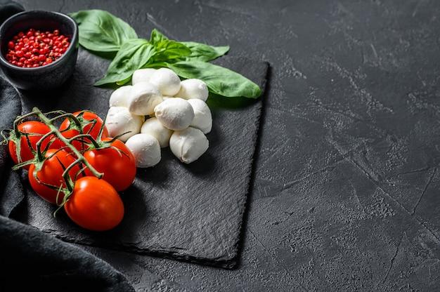 Ингредиенты для салата капрезе, сыра мини моцарелла, листьев базилика и помидоров черри. черный фон. вид сверху. копировать пространство