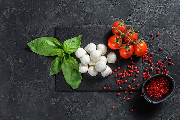 Ингредиенты для салата капрезе, сыра мини моцарелла, листьев базилика и помидоров черри. черный фон. вид сверху