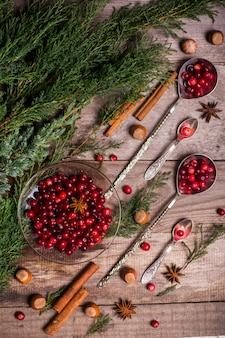 Ингредиенты на рождество, зимняя выпечка печенья. пряники, кексы, сезонные напитки. клюква, сушеные апельсины, корица, специи на деревянном столе, копией пространства вид сверху.