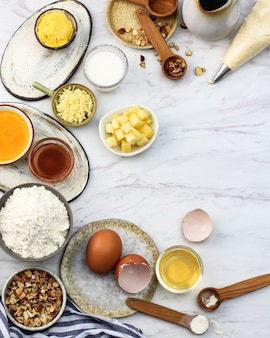 クリスマス冬のお祭りベーキングの材料。小麦粉、ブラウンシュガー、卵、チョコレートドロップ、バター、白い石またはコンクリートの背景にチーズ。上面図のコピースペース。