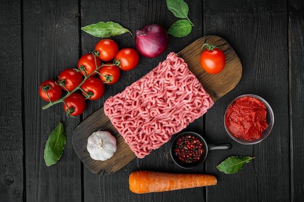 Ингредиенты для приготовления соуса болоньезе, мясного фарша, помидоров и зелени, на деревянной разделочной доске, на черном деревянном столе
