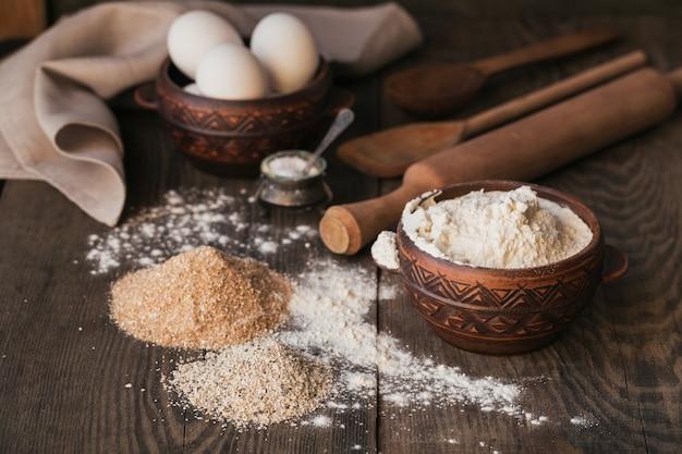 パンやクッキーを調理するための材料:素朴な木の表面にオートブラン、小麦粉、卵。健康食品のコンセプト。食品表面。