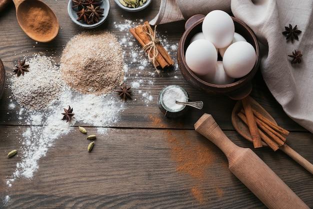 パンやクッキーを調理するための材料:素朴な木の表面にオートブラン、小麦粉、卵、スパイス。健康食品のコンセプト。食品表面。テキスト用のコピースペースを備えたフラットレイ