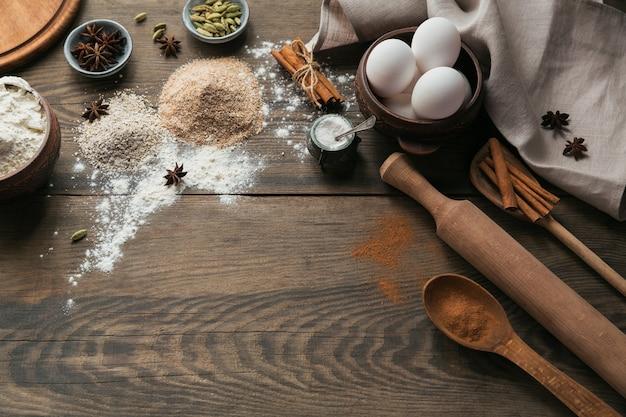 パンやクッキーを調理するための材料:素朴な木の表面にオートブラン、小麦粉、卵、スパイス。健康食品のコンセプト。食品表面。テキスト用のコピースペースのある上面図