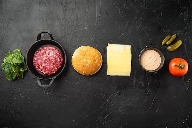 햄버거 요리 재료. 검은 돌에 다진 쇠고기 패티, 빵, 토마토, 허브 및 향신료 세트