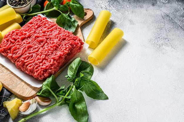 Ингредиенты для приготовления пасты каннеллони с говяжьим фаршем. итальянская кухня. серый фон вид сверху. копировать пространство