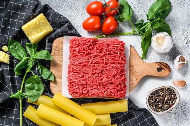 Ингредиенты для приготовления пасты каннеллони с говяжьим фаршем. итальянская кухня. серый фон вид сверху