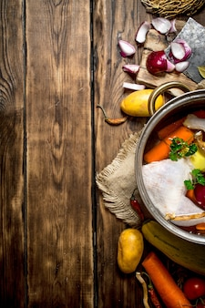 Ингредиенты для приготовления куриного супа с овощами и специями. на деревянном столе.