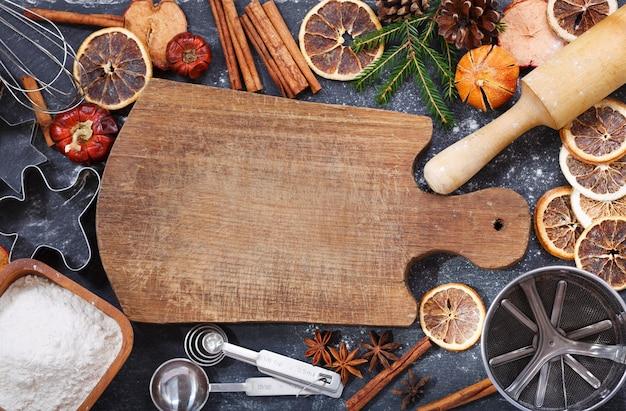 Ингредиенты для приготовления рождественской выпечки: пустая деревянная доска, мука, кухонная утварь и сухофрукты на темном фоне, вид сверху