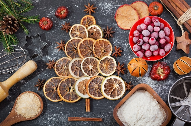Ингредиенты для приготовления рождественской выпечки ели из сухофруктов на темном столе